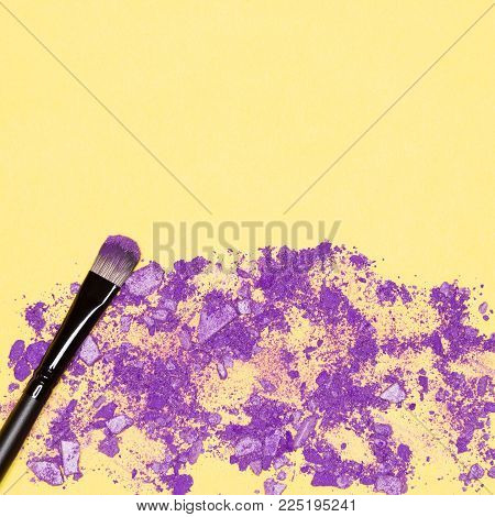 Makeup brush with crumbled ultra violet eyeshadow on yellow, empty space for text. Trendy makeup background
