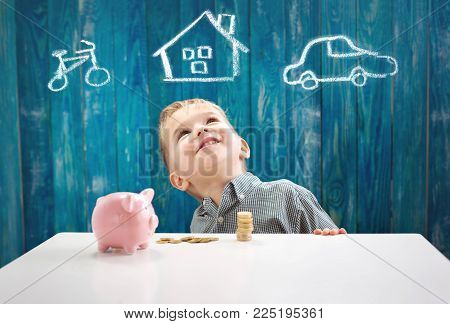 three years old child sitting st the table with money and a piggybank. Happy boy with euro coins. Kid dreaming about home