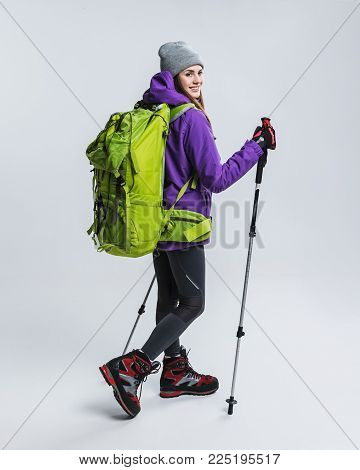 young hiker in sportswear with backpack and hiking sticks, isolated on grey