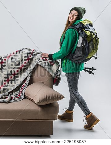 beautiful femele hiker with backpack at sofa with plaid