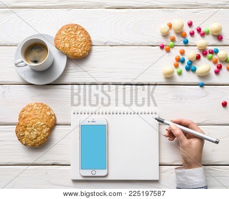 LONDON, UK NOVEMBER 27, 2017: Girl blogger making records to a diary, sitting in a cafe. Clipping path.