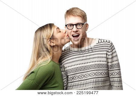 Studio Shot Of Happy Amazed Young Geeky Guy With Beard Wearing Eyeglasses And Sweater Opening Mouth