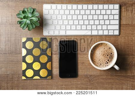 KYIV, UKRAINE - DECEMBER 18, 2017: Modern iPhone 8 Space Gray, notebook and cup of coffee on table