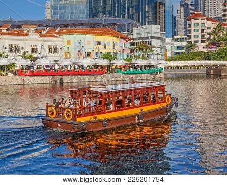 CLARKE QUAY, SINGAPORE - AUGUST 17, 2009: A traditional bumboat on the Singapore River passes Clarke Quay with a hotel and skyscrapers in the background.