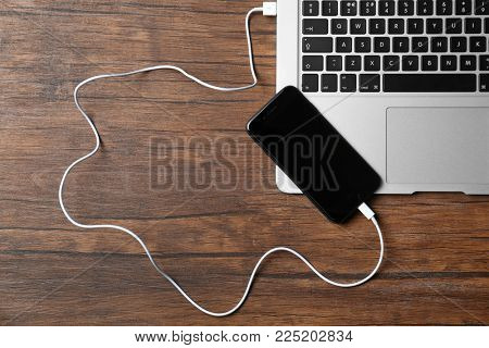 KYIV, UKRAINE - DECEMBER 18, 2017: iPhone 8 Space Gray connected to laptop on table