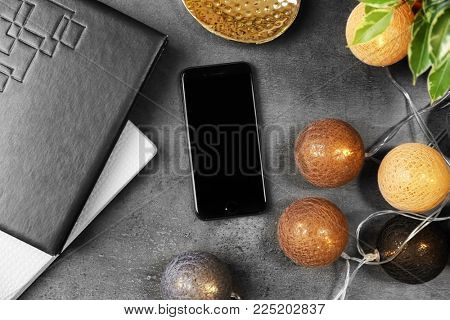 KYIV, UKRAINE - DECEMBER 18, 2017: Modern iPhone 8 Space Gray and garland on table