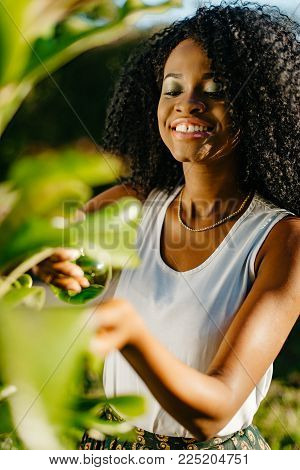Front View Of The Cheerful Attractive African Girl With Pretty Smile And Green Eye Shadows Using The