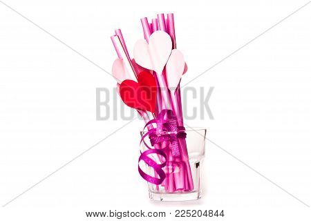 valentine's day holiday. pink and red sipping straws in a glass isolatedon white background