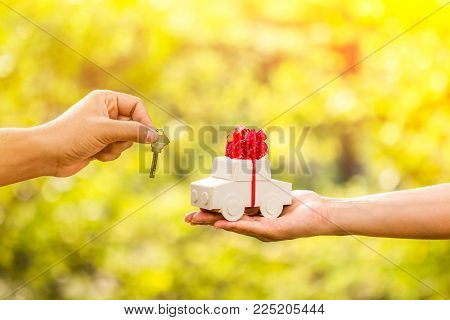 The buying a new chattel as a gift to family or the one loved concept, a man and a woman hand holding a car model tied with red ribbon and a key in the public park.