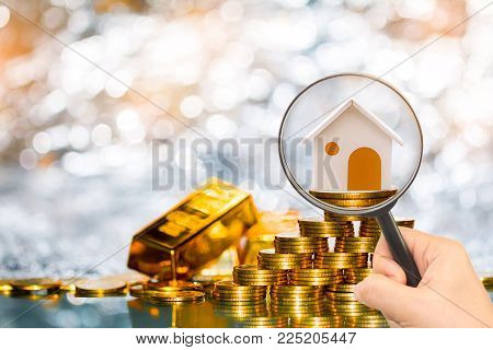 Stacking coin growing and gold bar and a magnifier searching for a new home on the beautiful bokeh background, Loans for real estate or save money for buy a new house to family in the future concept.