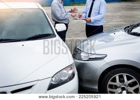 Insurance Agent Writing On Clipboard While Examining Car After Accident Claim Being Assessed And Pro