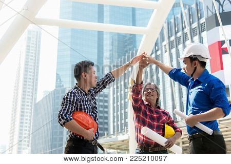 Architect engineer team stack hands join together and success in construction city site after planning project.  Workers security control.  City Background