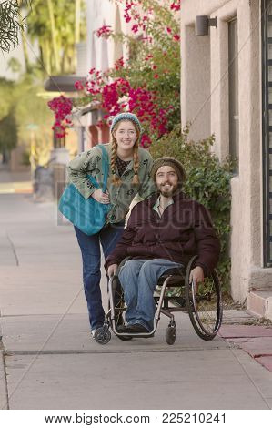 Woman with friend in wheelchair on city sidewalk
