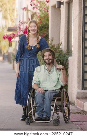 Woman with male friend in wheelchair on sidewalk