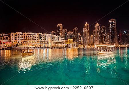 Singing fountains in Dubai. Dubai promenade singing fountains on the background of architecture. Traditional arabic boat Abra .