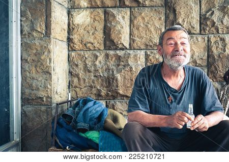 Homeless people. Happy and smiling poor homeless man sitting in the shadow of the building on the urban street in the city