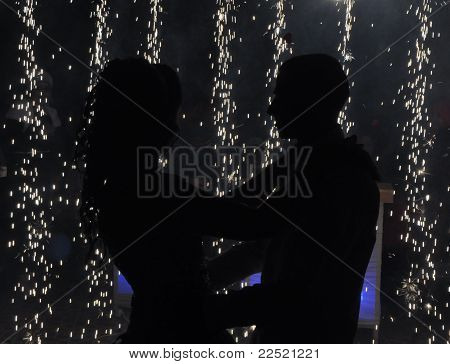 Silhouette of a man and a woman on a background of fireworks