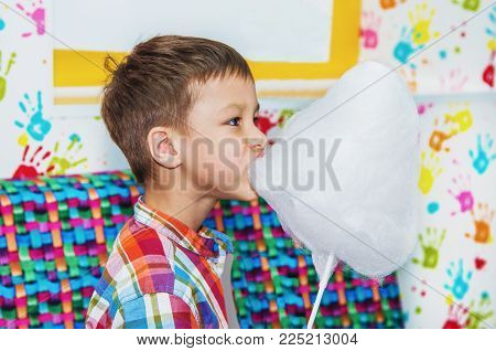 boy eating cotton candy in the room with colorful interior
