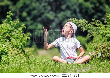 boy throws a raspberry into his mouth. Portrait of a  happy kid throwing berry in the air. Copy space for your text