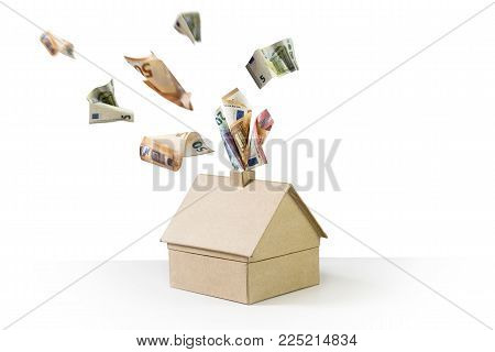 cardboard house with euro banknotes steaming out of the chimney and flying away on a white background, concept for heating costs and investment in thermal insulation, copy space