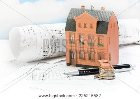 Investment in old building renovation, model house with architectural plans, coins and pen, real estate concept with copy space, selected focus