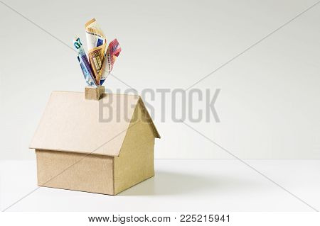 House made of cardboard and euro banknotes coming out of the chimney like steam on a gray background, concept for heating costs and thermal insulation, large copy space
