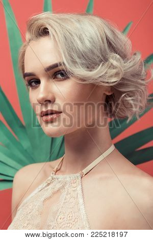 portrait of beautiful blonde woman in lace bra, isolated on red with palm leaf