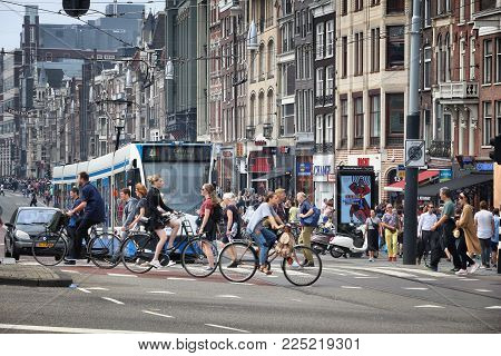 Amsterdam, Netherlands - July 7, 2017: People Visit Damrak Shopping Street In Amsterdam, Netherlands