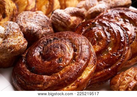 Assortment of french pastries. Delicious buttery croissants close-up. Fresh puff pastry baked croissant, buns on bakery table