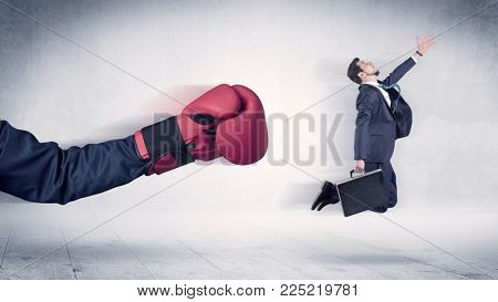 Huge Boxing Gloves punches innocent businessman concept