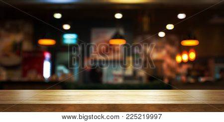 Empty wooden table top with blur coffee shop or restaurant interior background, Panoramic banner. Abstract background can be used product display.