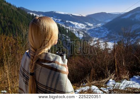 Winter mountain landscape photo of the blonde girl from the back in the plaid with a thermos and a cup of hot drink.