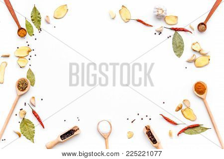 Seasoning background. Dry spices near ginger, garlic, rosemary on white background top view.