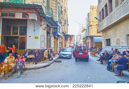 Alexandria, Egypt - December 17, 2017: The Narrow Street In Souq At Tork With Numerous Old Tables Of