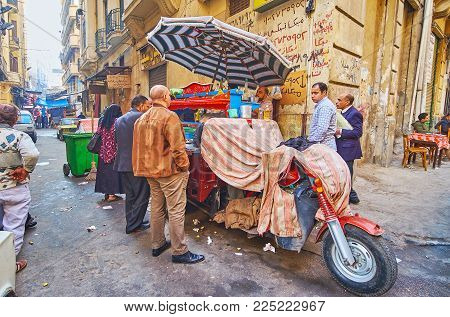 Alexandria, Egypt - December 17, 2017: The Cart Of Street Food Vendors In Souq At Tork, The Queue Of