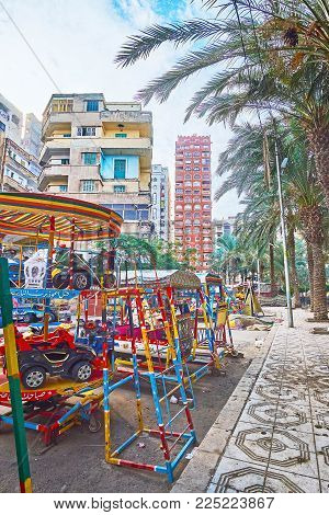 ALEXANDRIA, EGYPT - DECEMBER 17, 2017: The walk along the shady street with swings of local luna park and residential buildings on background, Anfoushi neighborhood, on December 17 in Alexandria.