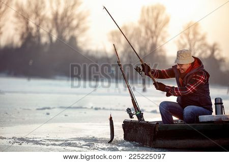 ice fishing on frozen lake- smiling senior fisherman catch fish