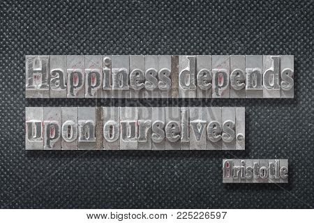Happiness depends upon ourselves - ancient Greek philosopher Aristotle quote made from metallic letterpress on dark background