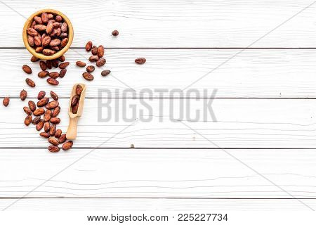 Roasted cocoa beans on white wooden background top view copy space. Raw material for cocoa powder. African or Latin American product.