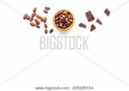 Roasted cocoa beans on white background top view copy space. Raw material for cocoa powder. African or Latin American product
