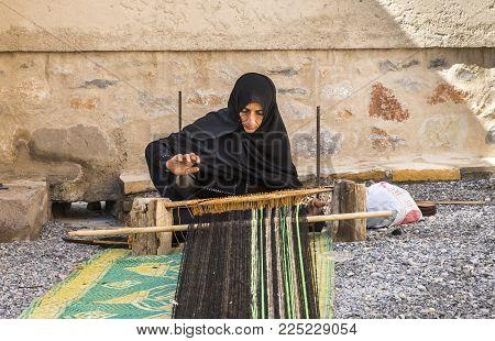 Nizwa, Oman, Febrary 2nd, 2018: Omani Woman Weaving A Carpet