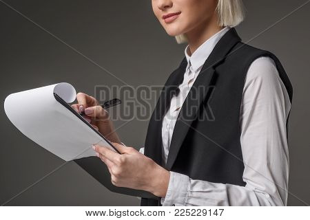 partial view of businesswoman with notepad isolated on grey
