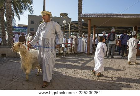 Nizwa, Oman, Febrary 2nd, 2018: Omani Man With His Goat Leaving The Traditional Goat Auction
