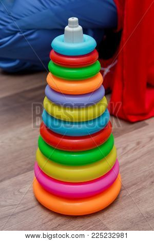 Colorful plastic rainbow toy pyramid for little kids on the blue background. Children's bright multi-colored toys. Children's multi-colored rainbow toy pyramid isolated on white background