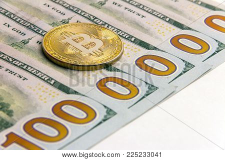 Gold bitcoin next to US banknotes. Five hundred dollar bills. One million dolars. Concept cryptocurrency exchange rate. White background.