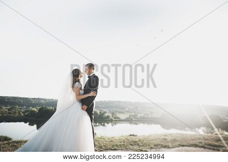 Wedding couple walking on bridge near lake on sunset at wedding day. Bride and groom in love.