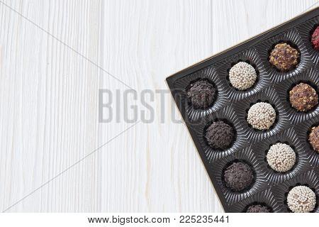 assorted dark milk chocolate candies on wooden background