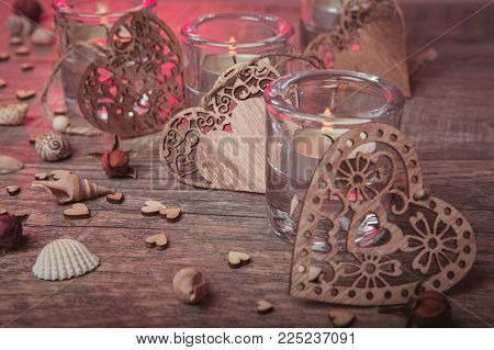 Spa concept in Valentine's Day, candles, handmade heart, seashells, setting for aroma therapy and salt massage on bed, relax and healthy care. Rustic style. Toned image in chocolate, red, pink tones.