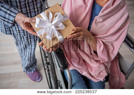 Top View Close Up Of Male And Female Hands Holding The Box With Bow. Woman Is Sitting In Invalid Cha