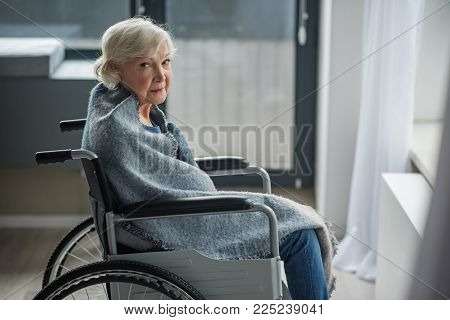 Cheerless Senior Female Sitting In Invalid Chair In Front Of The Window. She Is Looking At Camera Wi